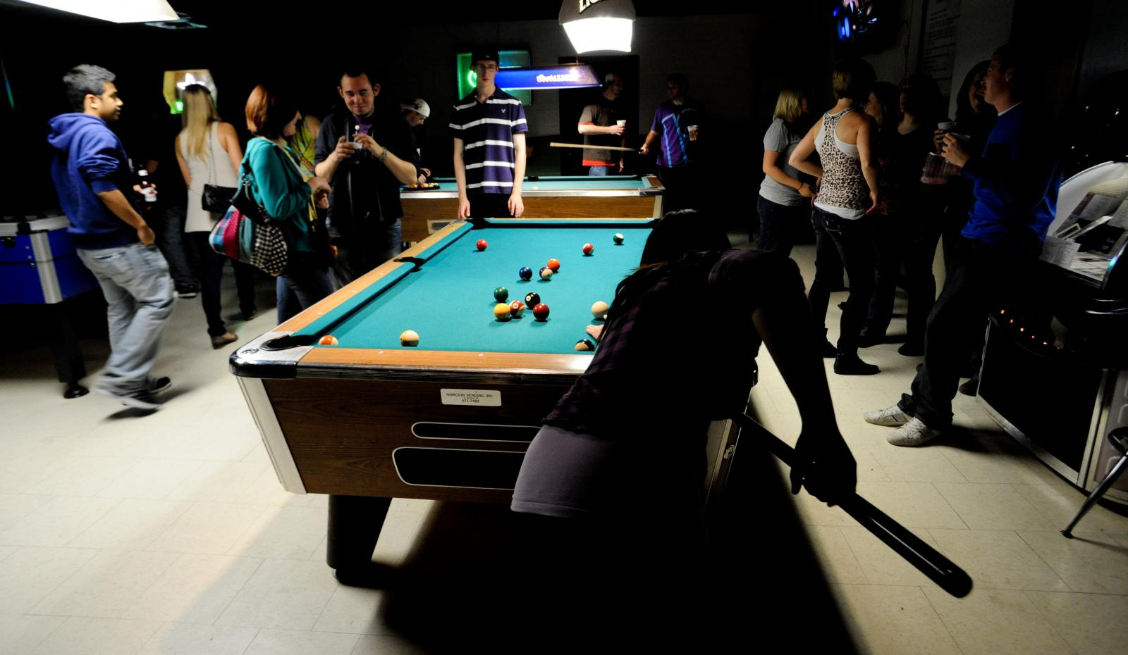 People stand around a pool table.