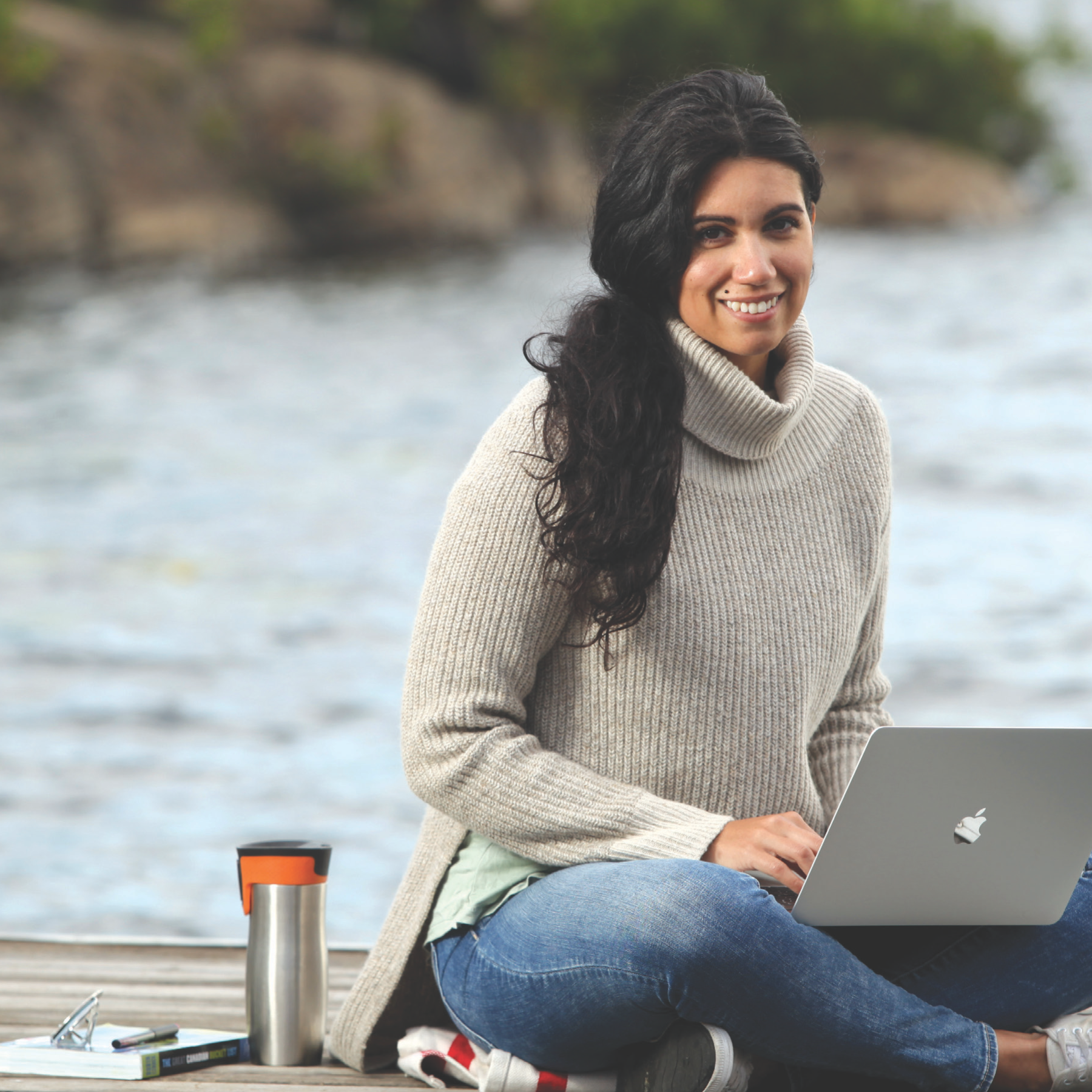 Woman sitting on a dock. She has a metal coffee container and a laptop. She is smiling.