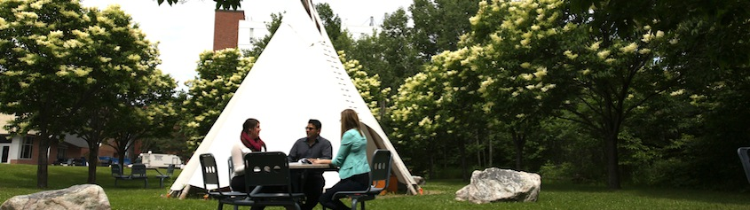 Three students at table in front of tepee